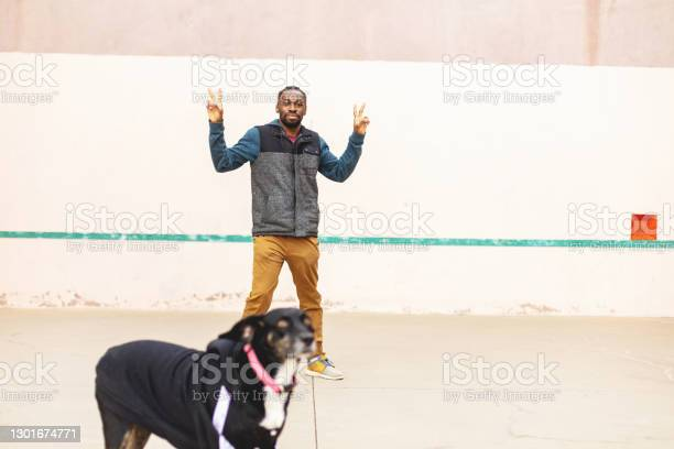 Generation Z Male Having Fun And Messing Around On A Hand Ball Court With Pet Dog Photo Series Stock Photo - Download Image Now
