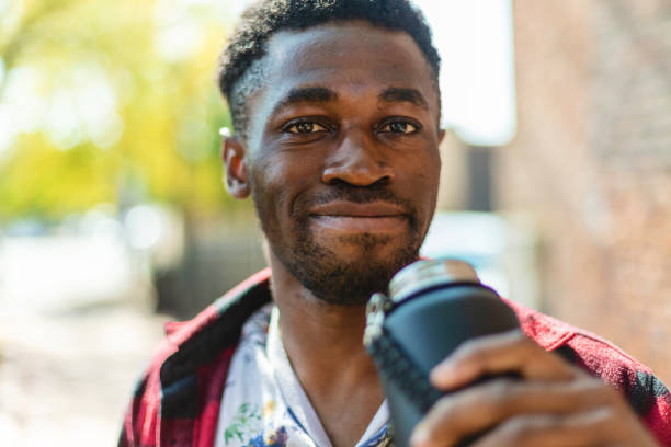 Generation Z Male of African Ethnicity Outdoors in City Holding Water Bottle Photo Series In Western Colorado Generation Z Male of African Ethnicity Outdoors in City Holding Water Bottle Photo Series Matching 4K Video Available (Shot with Canon 5DS 50.6mp photos professionally retouched - Lightroom / Photoshop - original size 5792 x 8688 downsampled as needed for clarity and select focus used for dramatic effect) eyecrave stock pictures, royalty-free photos & images