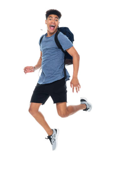 Generation z teenage boys high school student mid-air in front of white background wearing backpack stock photo