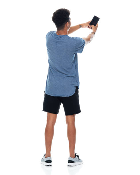 Generation z teenage boys photography standing in front of white background wearing t-shirt and using smart phone stock photo