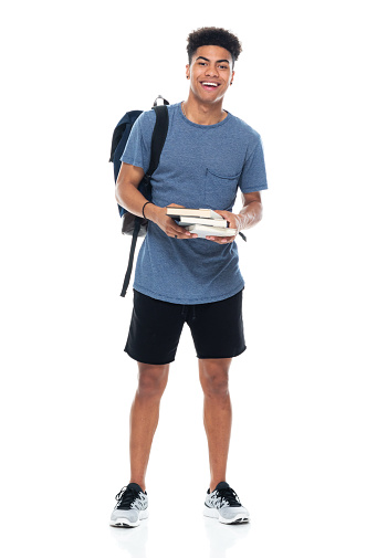 Full length of aged 18-19 years old with curly hair generation z teenage boys student standing in front of white background wearing backpack who is studying and holding bag