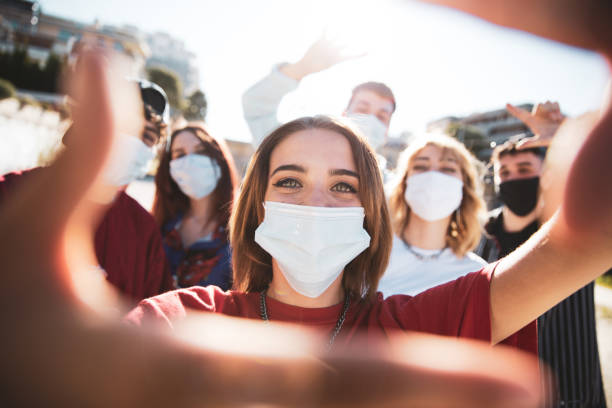 Generation Z teens wearing protective face masks stock photo
