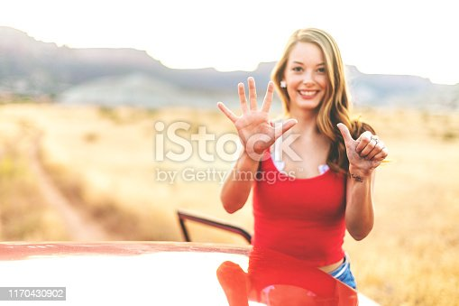 istock Generation Z Young Beautiful Female in non urban desert setting on dirt road in Western Colorado during the golden hour countdown 1170430902