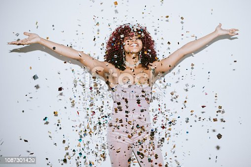 A young woman raises her hands in celebration as confetti falls on her.  Christmas or New Years festivities.