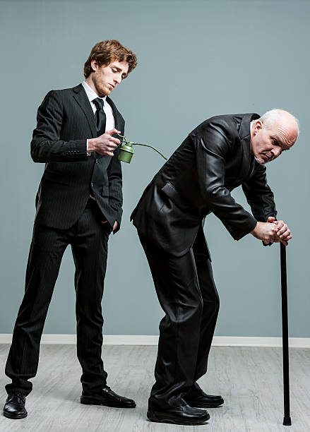 Generations concept of old and young men Generations concept of old and young men with a young businessman standing behind a pensioner using a stick applying oil to his back from an oil can deadweight stock pictures, royalty-free photos & images