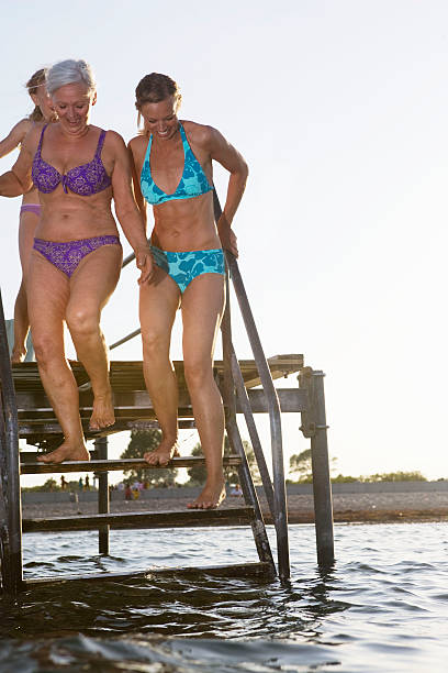 3 generations on jetty - older women bikini stock pictures, royalty-free photos & images