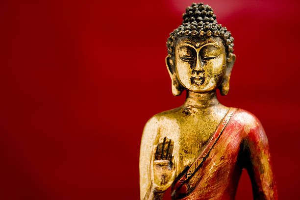A generic bronze and red colored zen Buddha statue on red stock photo