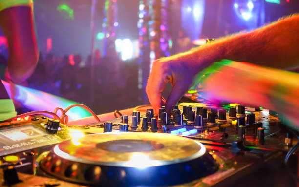 Generic dj playing party music at unrecognizable defocused disco club - Photo