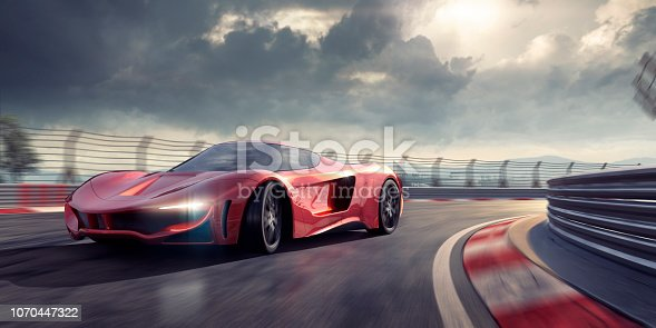 A generic red supercar driving at high speed around a bend of a racetrack under a dramatic stormy sky. The sports car could be an electric or hybrid and is turning towards the camera with it's headlights on. The action takes place under an evening sky. With motion blur effects.