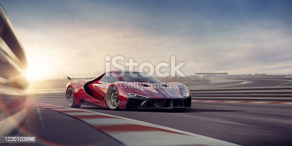 A close up image of a generic red sports car moving at high speed on a racetrack at dawn. There is motion blur to the track, and safety fence as well as the wheels on the vehicle. The background is track is out of focus.
