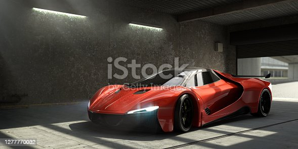 A generic luxury red sports car, with headlights on, having just parked in an empty concrete / industrial garage space with roller shutter door, which is still partially up revealing out of focus background. Light stream in through a rood window with slight dusty haze.