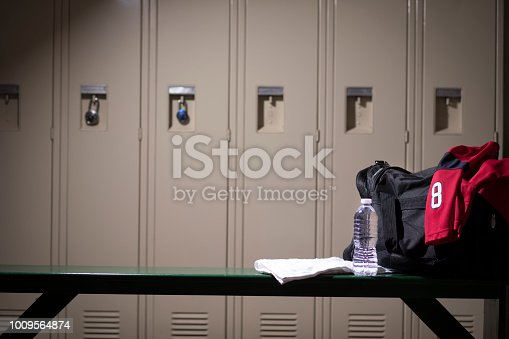 Various sports equipment on bench inside high school or college gymnasium locker room.   Items include:  sports jersey, water, towel, gym bag..