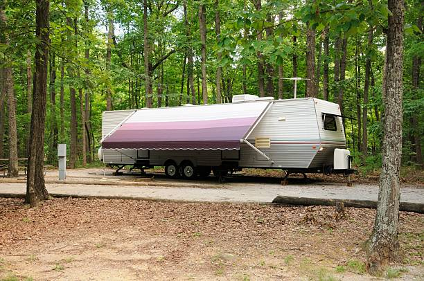 Generic travel trailer with awning in campground stock photo