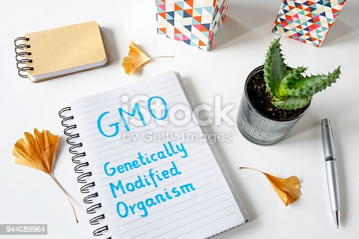 GMO Genetically Modified Organism written in notebook on white table
