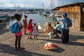 2019 Geneva, Switzerland.  Tourist feeding swans in the harbour near the lakeshore promenade and the jetties in Geneva.