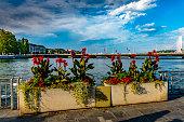 2019 Geneva, Switzerland.  Flower displays in the foreground of the harbour near the lakeshore promenade and the jetties in Geneva.