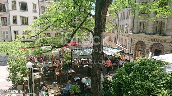 Geneva, Switzerland - June 20, 2020: People are sitting in a café in a square in the city center, eating and drinking, enjoying the nice, sunny day.