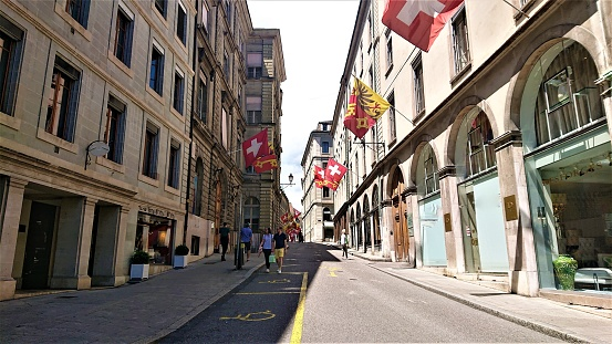 Geneva, Switzerland - June 20, 2020: People are walking on a street in the city center, enjoying the nice, sunny day.
