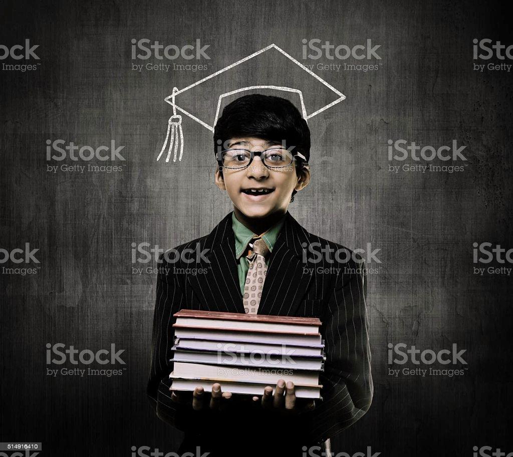 Genius Little Boy Holding Books Wearing Graduation Cap, Chalkboard stock photo