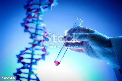 Scientist holding genetic sample in a test tube with image of DNA in background.