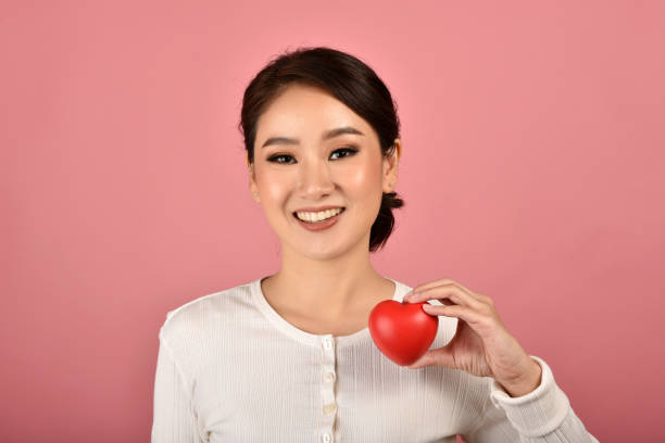 Gentle asian woman holding red heart, Happy smiling girl showing love sign to support and encourage, Cardiac health checkup. stock photo