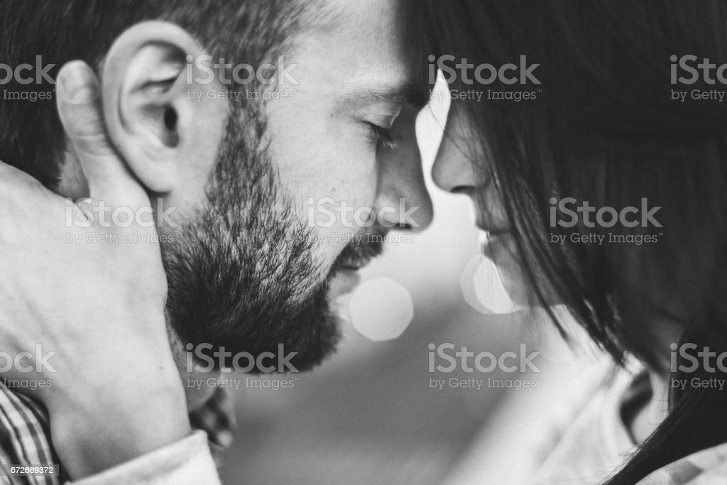 Gentle close-up portrait of man and woman together, happy, looking at each other. Black and white toning stock photo