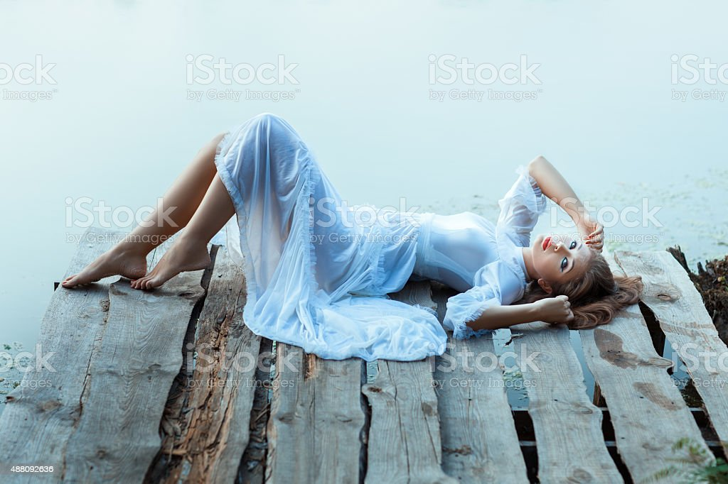 Gentle girl in white dress lying on a wooden pier. stock photo
