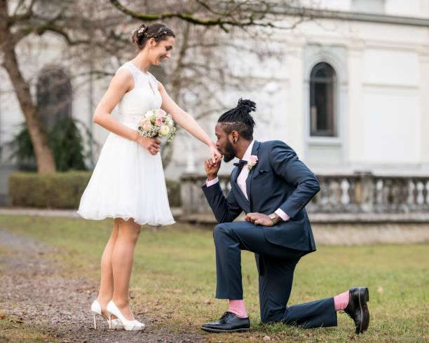Suave novio arrodillado delante de la novia - foto de stock