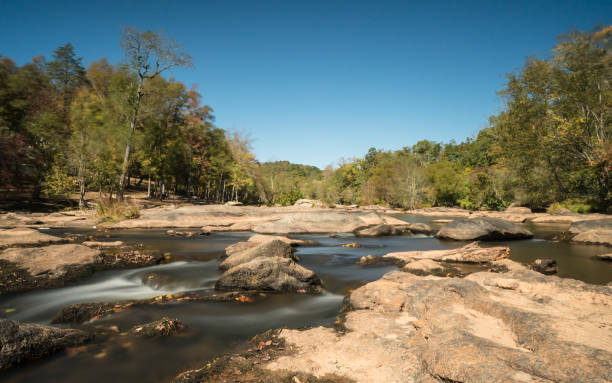 gentle river with many rocks and flowing water gentle South Tyger River with many rocks and flowing low water and forest in the background spartanburg stock pictures, royalty-free photos & images