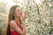 Portrait of a beautiful young woman among trees in bloom, enjoying the scent of blossoming orchard in spring.