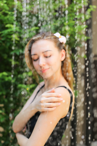 545091450 istock photo gentle soft portrait of girl who is bathed in street in shower w 1186393817