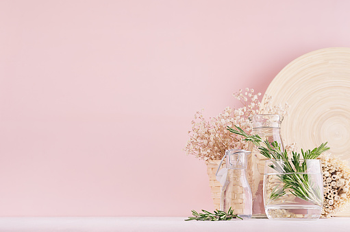 Gentle spring vanilla background of fresh bouquet rosemary and natural beige bamboo home decoration in glass on white table and pink wall.
