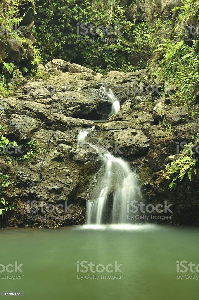Gentle waterfall flows over rocks in Hawaii royalty-free stock photo