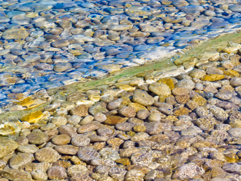Gentle wave across smooth rocks in shallow water
