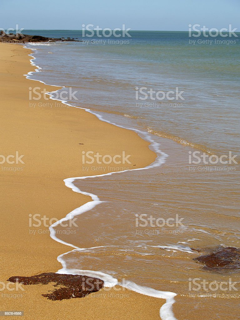 Gentle Waves Lap on a Yellow Sand Beach royalty-free stock photo