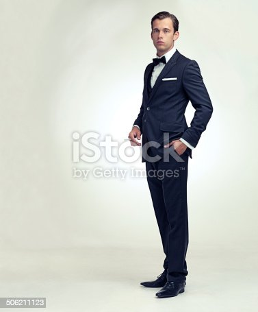 A full length studio portrait of a handsome young gentleman in a pinstripe suit holding a cigarette