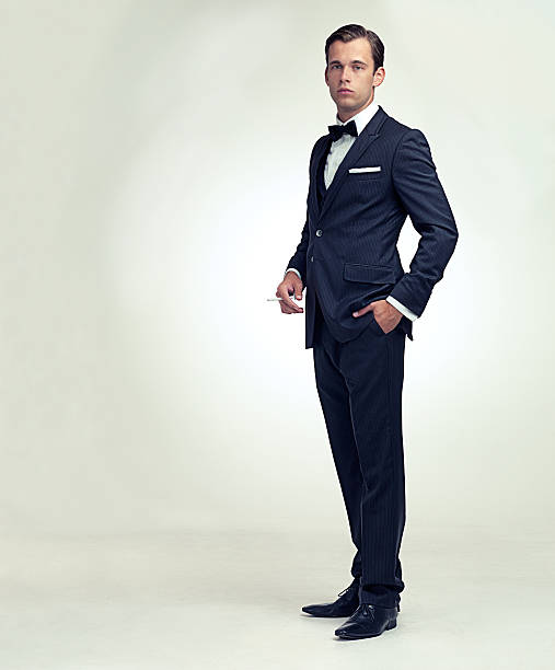 Gentleman and his cigarette A full length studio portrait of a handsome young gentleman in a pinstripe suit holding a cigarette evening wear stock pictures, royalty-free photos & images