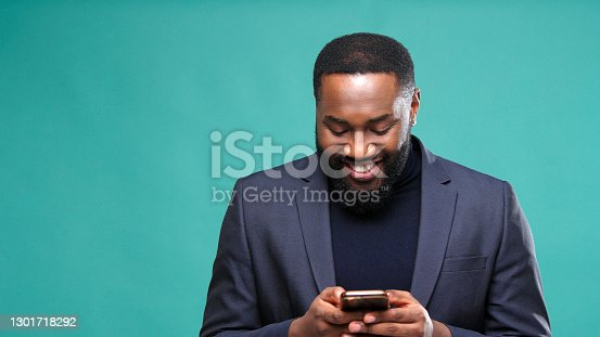 Happy dark skinned gentleman holds smartphone and writes text message smiling at audition break on green background closeup