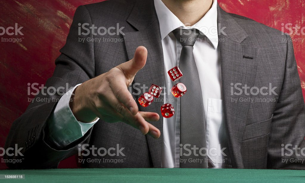 A gentleman in a suit rolling dice stock photo