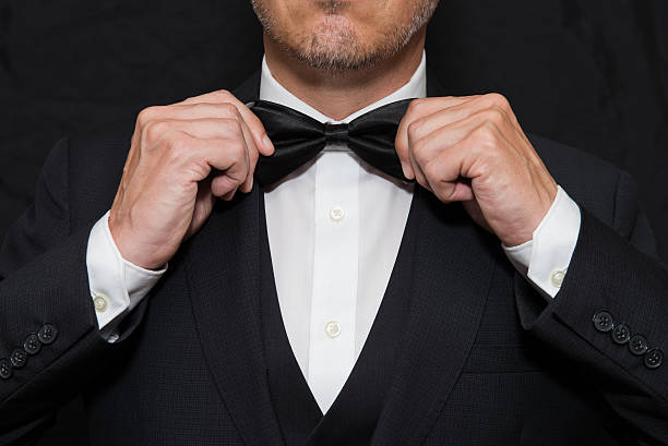 Gentleman in Black Tie Straightens His Bowtie stock photo