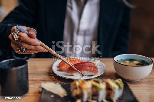 One man, gentleman sitting in restaurant alone, he is eating sushi.