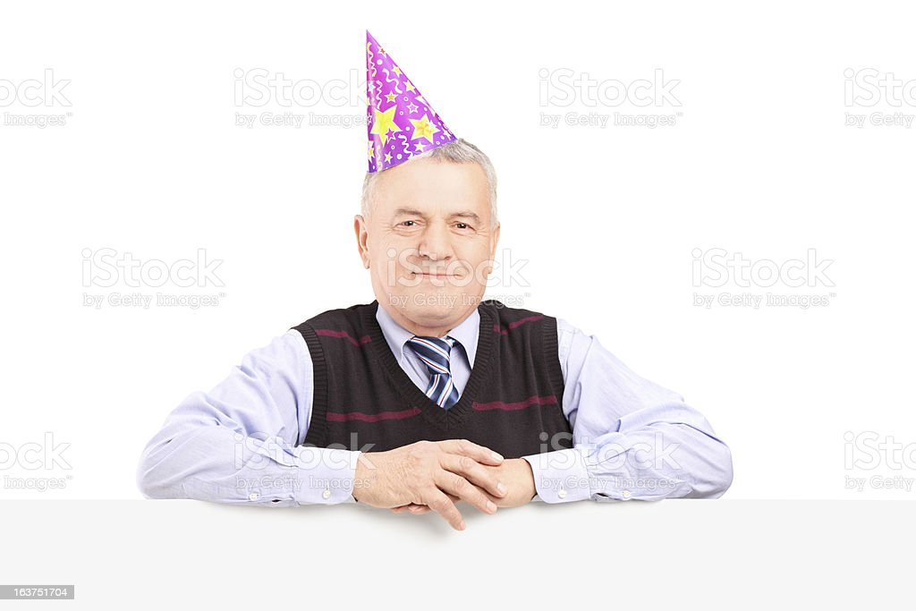 Gentleman wearing party hat and posing behind a panel royalty-free stock photo