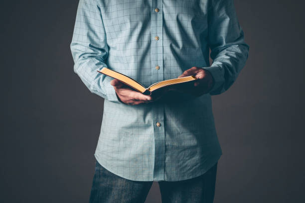 Gentleman with a bible open in his hands stock photo