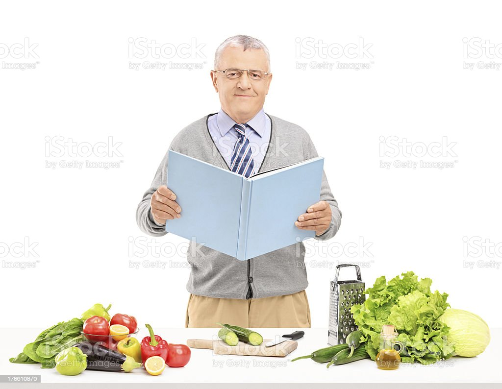 Gentleman with cookbook preparing salad royalty-free stock photo