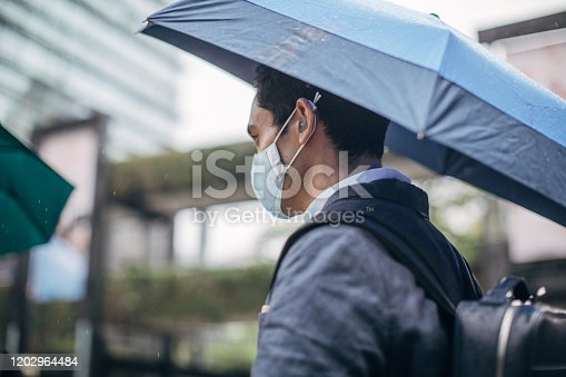 One man, young Taiwanese businessman downtown in Taipei, holding blue umbrella and wearing a pollution mask.