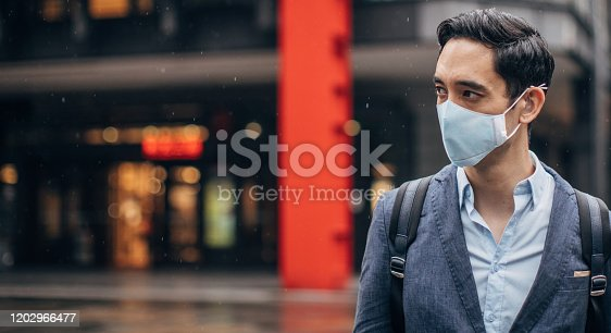 One man, young Taiwanese businessman downtown in Taipei, wearing a pollution mask.