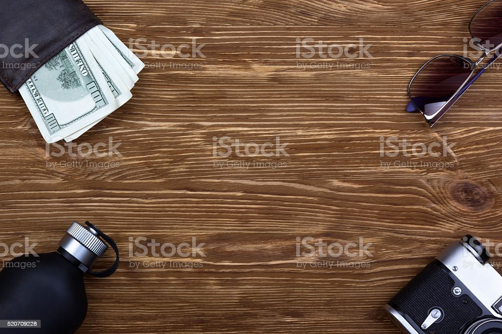 gentlemanly set:  sunglasses, perfume, wallet, money,camera on wooden background stock photo