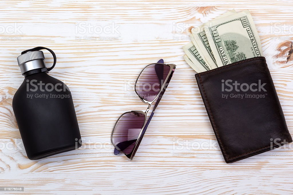 gentlemanly set:  sunglasses, perfume, wallet with money on wooden background stock photo