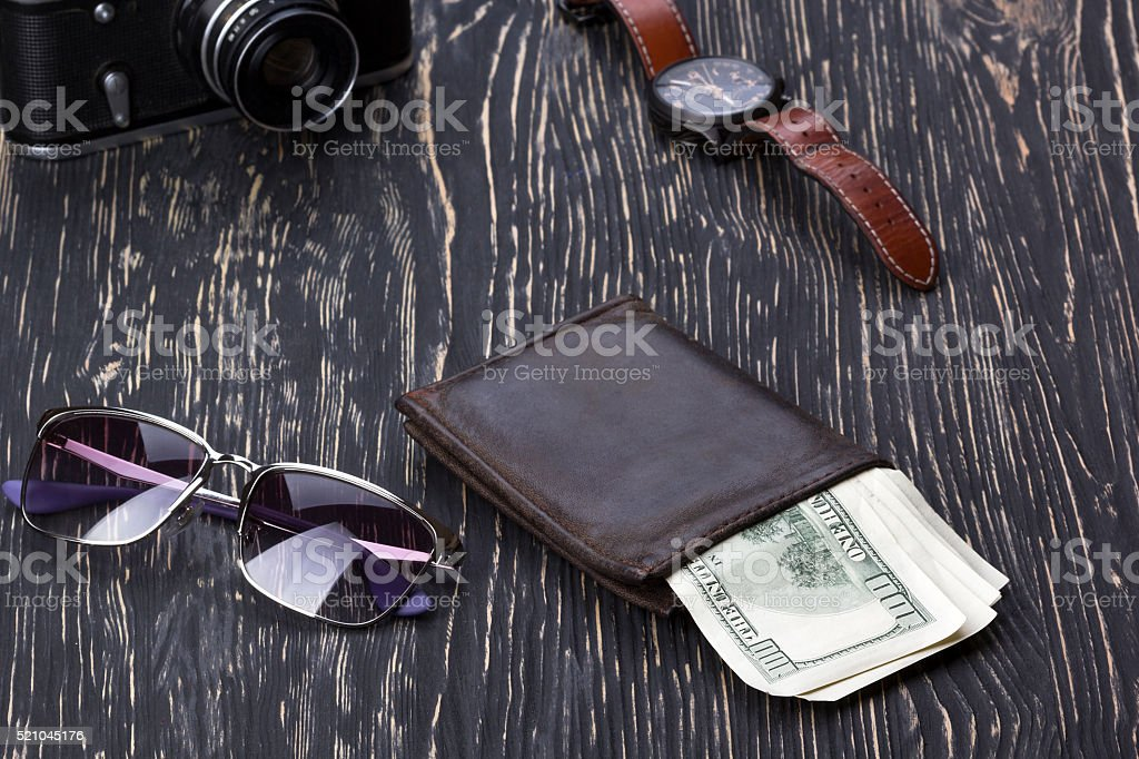 gentlemanly set:  sunglasses, wallet, camera, watch on wooden background stock photo