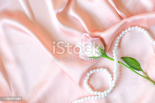 A delicate pink rose with a pearl necklace on a powder-colored satin fabric.